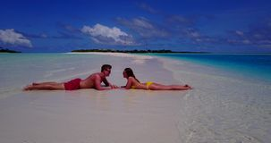 V14831 two 2 people laying romantic young couple sunbathing on a tropical island of white sand beach and blue sky and. Two 2 people laying romantic young couple stock video footage
