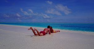 V14839 two 2 people laying romantic young couple sunbathing on a tropical island of white sand beach and blue sky and. Two 2 people laying romantic young couple stock video