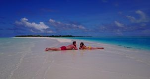 V14843 two 2 people laying romantic young couple sunbathing on a tropical island of white sand beach and blue sky and. Two 2 people laying romantic young couple stock video