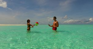 V14851 two 2 people playing ball romantic young couple on a tropical island of white sand beach and blue sky and sea. Two 2 people playing ball romantic young stock footage