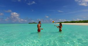 V14853 two 2 people playing ball romantic young couple on a tropical island of white sand beach and blue sky and sea. Two 2 people playing ball romantic young stock video footage