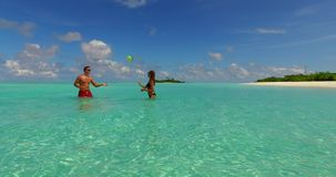 V14855 two 2 people playing ball romantic young couple on a tropical island of white sand beach and blue sky and sea. Two 2 people playing ball romantic young stock video