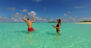V14858 two 2 people playing ball romantic young couple on a tropical island of white sand beach and blue sky and sea. Two 2 people playing ball romantic young stock video footage