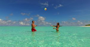 V14845 two 2 people playing ball romantic young couple on a tropical island of white sand beach and blue sky and sea. Two 2 people playing ball romantic young stock video