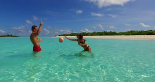V14860 two 2 people playing ball romantic young couple on a tropical island of white sand beach and blue sky and sea. Two 2 people playing ball romantic young stock video