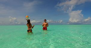 V14850 two 2 people playing ball romantic young couple on a tropical island of white sand beach and blue sky and sea. Two 2 people playing ball romantic young stock video footage