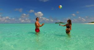 V14858 two 2 people playing ball romantic young couple on a tropical island of white sand beach and blue sky and sea stock images