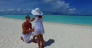 V14864 two 2 people proposal marriage romantic young couple holding hands on a tropical island of white sand beach and stock footage