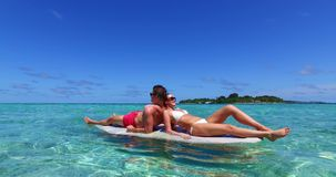 V11346 two 2 people romantic young people couple paddleboard surfboard with drone aerial flying view on a tropical. Two 2 people romantic young people couple stock photos