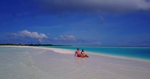 V14912 two 2 people sitting together a romantic young couple on a tropical island of white sand beach and blue sky and. Two 2 people sitting together a romantic stock footage