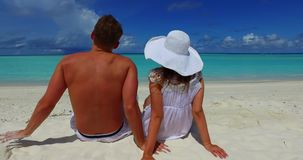 V14870 two 2 people sitting together a romantic young couple on a tropical island of white sand beach and blue sky and. Two 2 people sitting together a romantic stock video