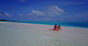 V14901 two 2 people sitting together a romantic young couple on a tropical island of white sand beach and blue sky and. Two 2 people sitting together a romantic stock footage