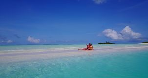 V14874 two 2 people sitting together a romantic young couple on a tropical island of white sand beach and blue sky and. Two 2 people sitting together a romantic stock video