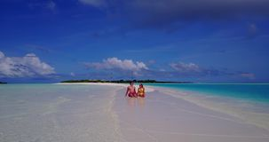 V14911 two 2 people sitting together a romantic young couple on a tropical island of white sand beach and blue sky and. Two 2 people sitting together a romantic stock video