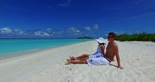 V14892 two 2 people sitting together a romantic young couple on a tropical island of white sand beach and blue sky and. Two 2 people sitting together a romantic stock footage