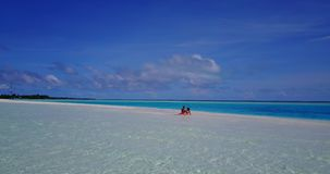 V14887 two 2 people sitting together a romantic young couple on a tropical island of white sand beach and blue sky and. Two 2 people sitting together a romantic stock footage