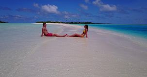 V14906 two 2 people sitting together a romantic young couple on a tropical island of white sand beach and blue sky and Royalty Free Stock Photography