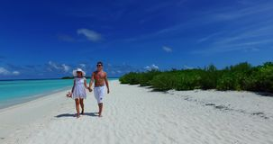 V12618 two 2 people walking romantic young people couple holding hands on a tropical island of white sand beach and blue stock video