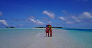 V12638 two 2 people walking romantic young people couple holding hands on a tropical island of white sand beach and blue. Two 2 people walking romantic young stock video