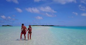 V12661 two 2 people walking romantic young people couple holding hands on a tropical island of white sand beach and blue. Two 2 people walking romantic young stock footage