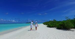 V12644 two 2 people walking romantic young people couple holding hands on a tropical island of white sand beach and blue. Two 2 people walking romantic young stock video