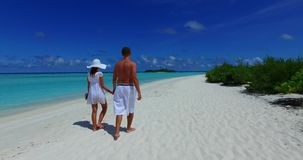 V12613 two 2 people walking romantic young people couple holding hands on a tropical island of white sand beach and blue. Two 2 people walking romantic young stock video footage