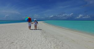 V12631 two 2 people walking romantic young people couple holding hands on a tropical island of white sand beach and blue. Two 2 people walking romantic young stock footage