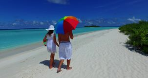 V12626 two 2 people walking romantic young people couple holding hands on a tropical island of white sand beach and blue. Two 2 people walking romantic young stock video footage