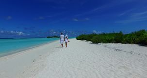 V12622 two 2 people walking romantic young people couple holding hands on a tropical island of white sand beach and blue. Two 2 people walking romantic young stock video footage