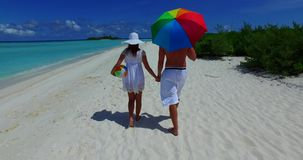 V12625 two 2 people walking romantic young people couple holding hands on a tropical island of white sand beach and blue. Two 2 people walking romantic young stock footage