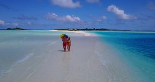V12652 two 2 people walking romantic young people couple holding hands on a tropical island of white sand beach and blue. Two 2 people walking romantic young stock video