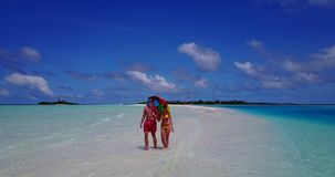 V12636 two 2 people walking romantic young people couple holding hands on a tropical island of white sand beach and blue stock footage