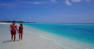 V12668 two 2 people walking romantic young people couple holding hands on a tropical island of white sand beach and blue stock video