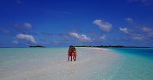 V12635 two 2 people walking romantic young people couple holding hands on a tropical island of white sand beach and blue stock video footage