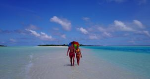 V12639 two 2 people walking romantic young people couple holding hands on a tropical island of white sand beach and blue stock video footage