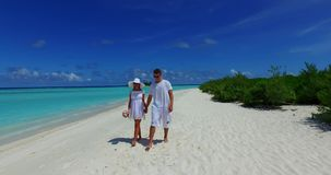 V12655 two 2 people walking romantic young people couple holding hands on a tropical island of white sand beach and blue. Two 2 people walking romantic young stock footage