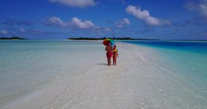 V12658 two 2 people walking romantic young people couple holding hands on a tropical island of white sand beach and blue stock footage
