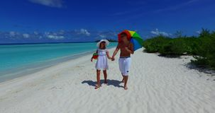 V12628 two 2 people walking romantic young people couple holding hands on a tropical island of white sand beach and blue stock footage