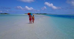 V12659 two 2 people walking romantic young people couple holding hands on a tropical island of white sand beach and blue stock footage