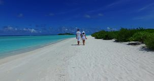 V12633 two 2 people walking romantic young people couple holding hands on a tropical island of white sand beach and blue. Two 2 people walking romantic young stock video footage