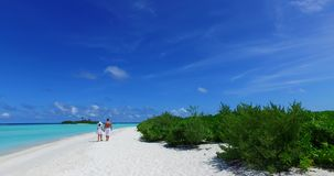 V12615 two 2 people walking romantic young people couple holding hands on a tropical island of white sand beach and blue. Two 2 people walking romantic young stock video footage