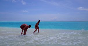 V12667 two 2 people walking romantic young people couple holding hands on a tropical island of white sand beach and blue. Two 2 people walking romantic young stock video