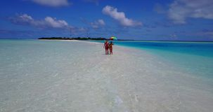 V12656 two 2 people walking romantic young people couple holding hands on a tropical island of white sand beach and blue Stock Photo