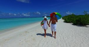 V12628 two 2 people walking romantic young people couple holding hands on a tropical island of white sand beach and blue Royalty Free Stock Image