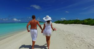V12619 two 2 people walking romantic young people couple holding hands on a tropical island of white sand beach and blue Royalty Free Stock Images