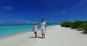 V12666 two 2 people walking romantic young people couple holding hands on a tropical island of white sand beach and blue Stock Image
