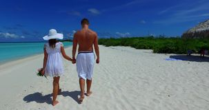 V12672 two 2 people walking romantic young people couple holding hands on a tropical island of white sand beach and blue Royalty Free Stock Images