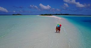 V09037 Two 2 romantic young people couple walking holding hands with drone aerial flying view on a tropical stock video