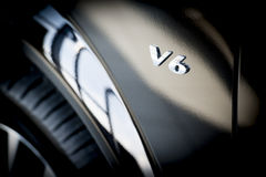 V6 Emblem on side of new car Stock Photography