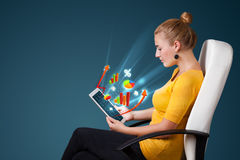 Молодая женщина смотря самомоднейшую таблетку с абстрактными светами и va Стоковое фото RF
